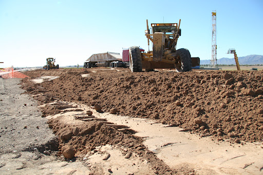 Grader smooths earth after relocating underground utilities.