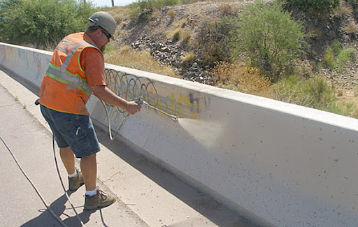 Worker sprays paint over graffiti on a low wall.