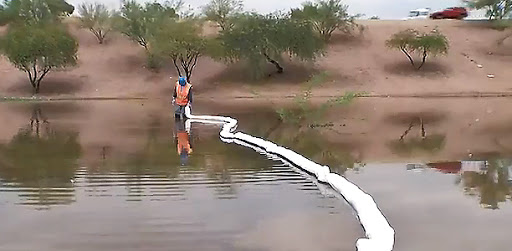 Hazmat worker places retaining float in water of overflow basin.
