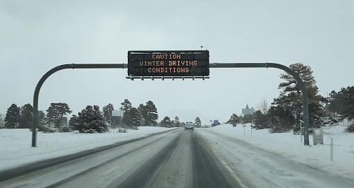 Winter Driving Conditions sign over snowy roadway