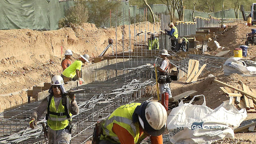Construction workers add to rebar forms for freeway expansion.