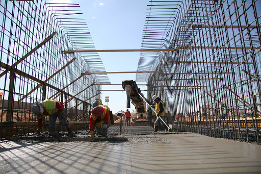Workers smooth concrete surrounded by rebar framework for walls