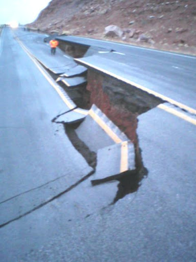 ADOT worker standing next to road damage from the landslide