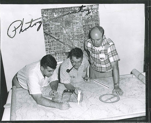 Three men working on a mylar map.