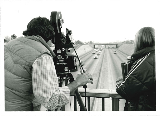 Black and White photo of video being taken over one of the state roads.