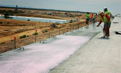 Workers spraying concrete curing compound