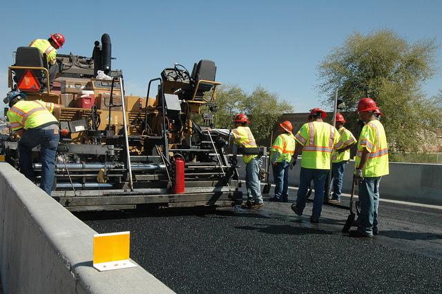 Crew laying pavement