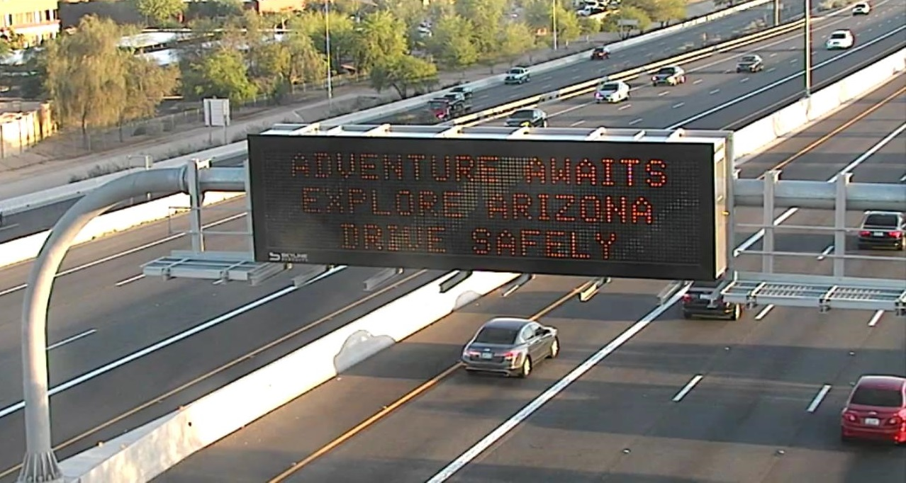 Highway Sign: Adventure Awaits - Explore Arizona - Drive Safely