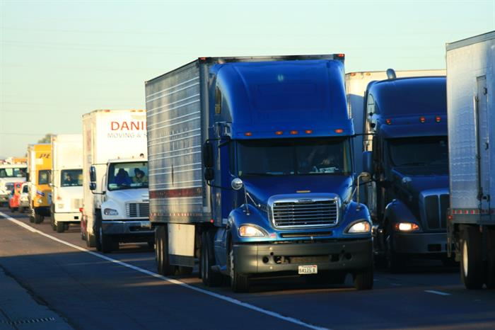 A line of tractor trailers on the highway