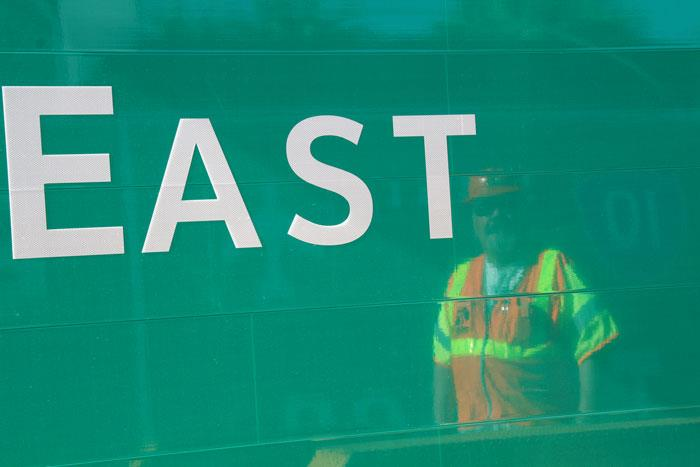 ADOT worker reflection in Highway sign.