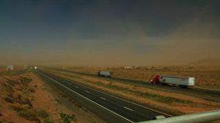 Tractor trailers on I-10 head towards a dust storm.