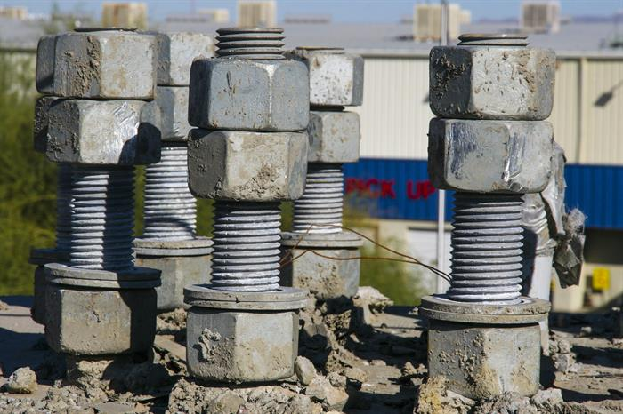 Close-up of nuts and bolts used to connect streetlight posts to the concrete base the light sits on.