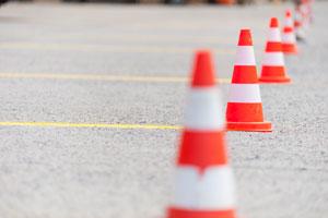 Orange and white striped traffic cones in a vertical line.