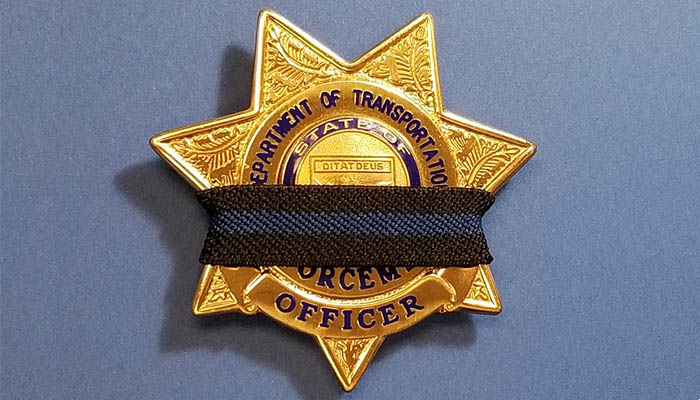 Black band across an Enforcement Officer badge.