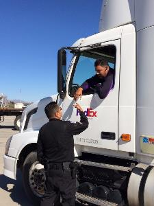 Port of Entry officer shakes hands with Truck driver.