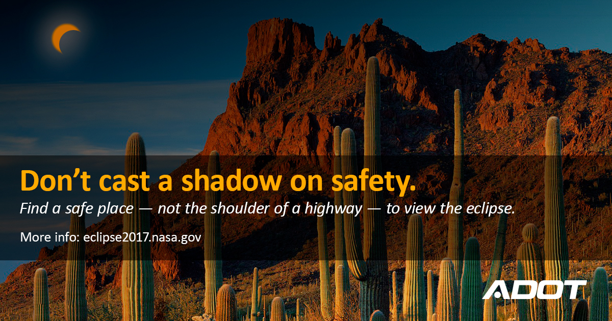 The sky darkens over rock buttes and saquaro cactus during a lunar eclipse. Don't cast a shadow on safety.  Find a safe place - not the shoulder of a highway - to view the eclipse.