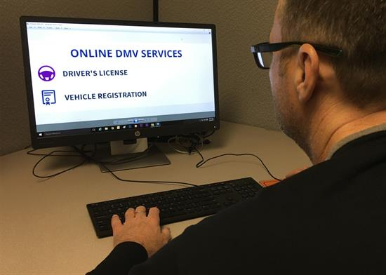 Man looking at computer screen with mock DMV web site.