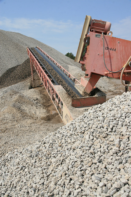 A rock crusher breaks concrete that was part of the old roadway into small pieces that serve as a base layer.
