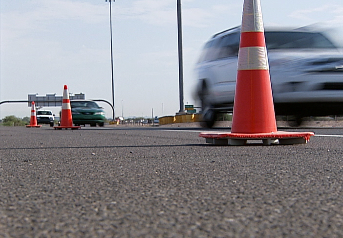 Cars wiz past traffic cones.