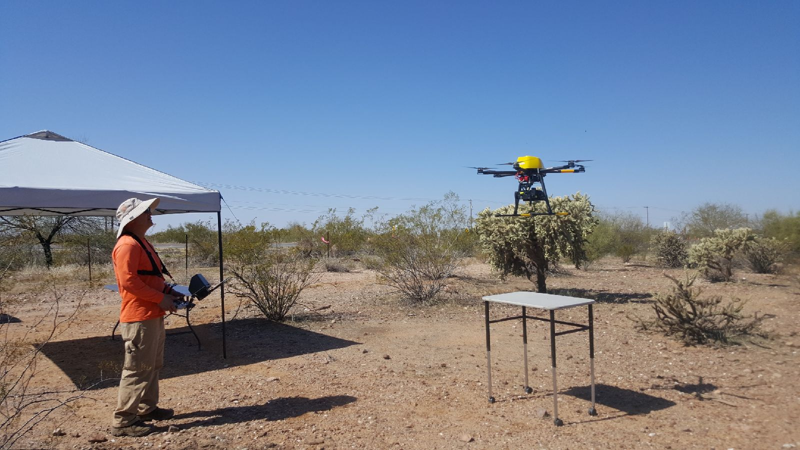 Employee launches drone in the desert.
