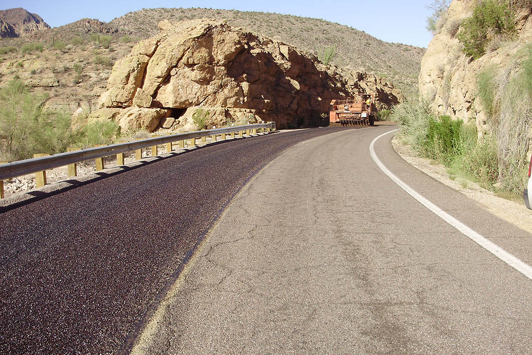 Large paving vehicle applies tack coat to SR 88.