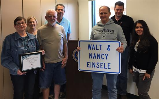 Walt and Nancy Einsele with Alvin Stump, district engineer for the Northwest District, holding a sign with their names.