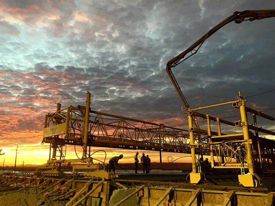 Vibrant sunset behind crew working on a Bid-Well 4800 smoothing cement.