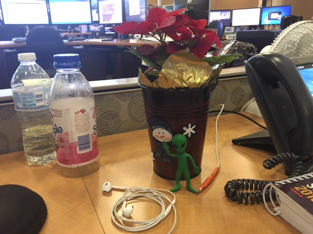 Alien figure decorates a poinsettia.