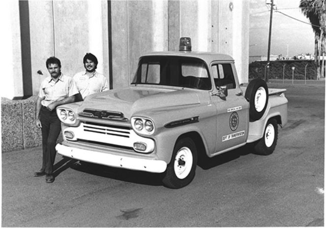Two ADOT employees standing by yellow 1959 Chevrolet Apache pickup