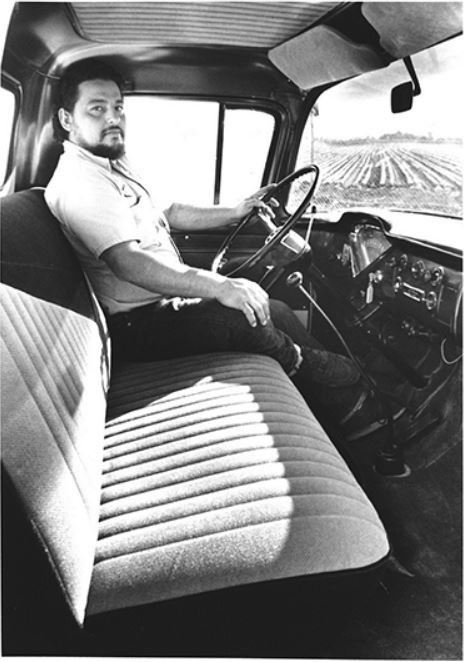Interior view of the 1959 Chevrolet Apache pickup with an employee behind the wheel.