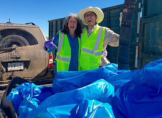 Two volunteers happily display the bags of litter they have picked up.