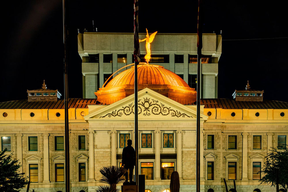 Night shot of the Arizona Capitol Building with the dome lit in orange lights for National Work Zone Awareness Week.