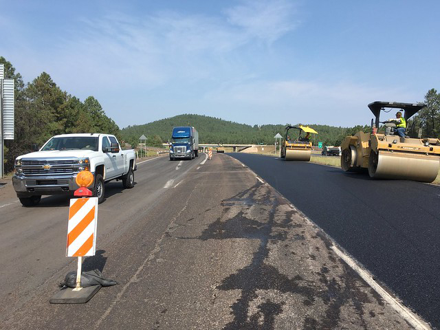 Traffic moves past work zone where crews smooth new surface.