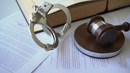 Dealer/Title Fraud Investigations - Handcuffs, book and gavel on papers
