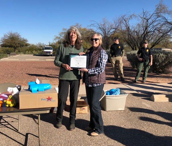 An Adopt a Highway volunteer receives a certificate from the program manager.