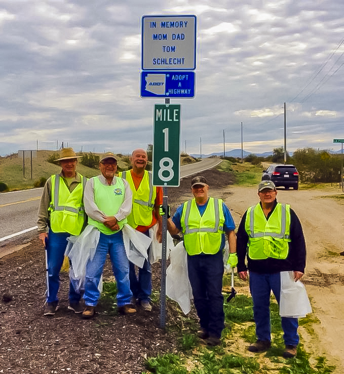 The five Schlecht brothers next to their family's Adopt a Highway sign
