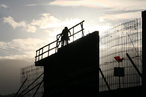 Worker atop a sound wall under construction
