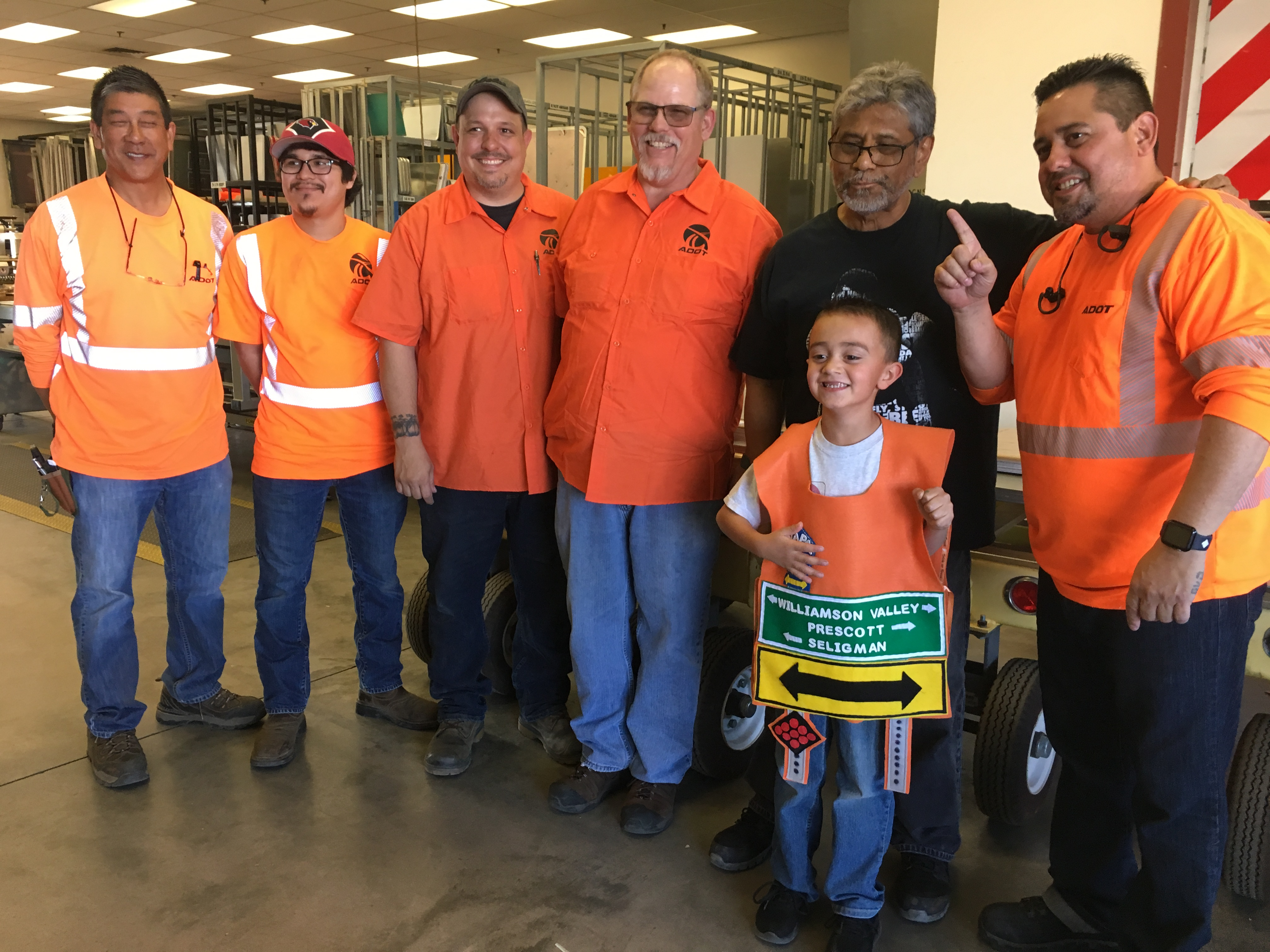 ADOT Sign Factory techs pose with a little boy who loves signs