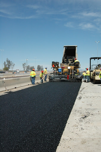 Rubberized asphalt is placed on an off- ramp in the west Valley last March.