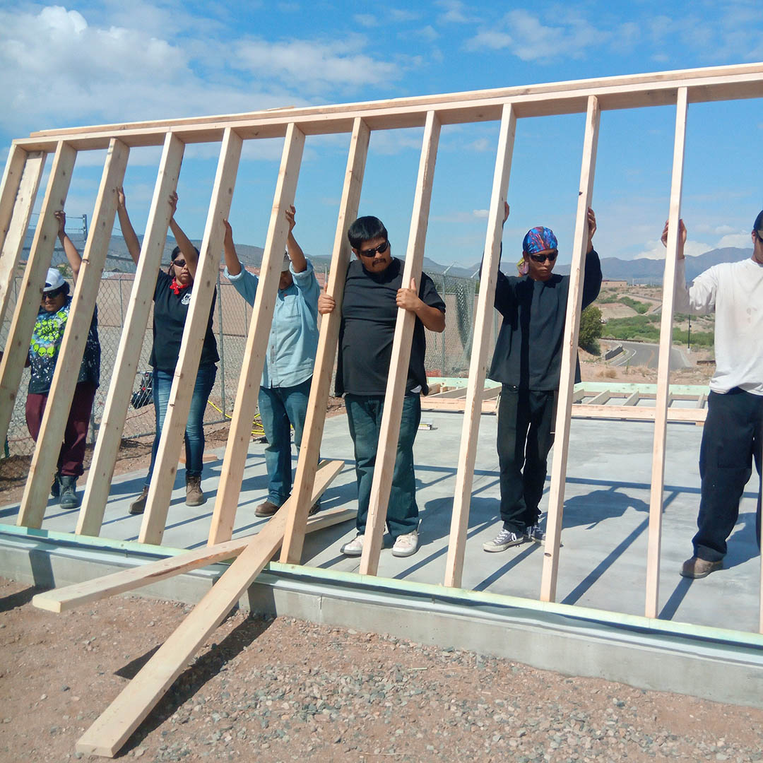 Student with the Yavapai-Apache Construction Academy lift wall frame into place.