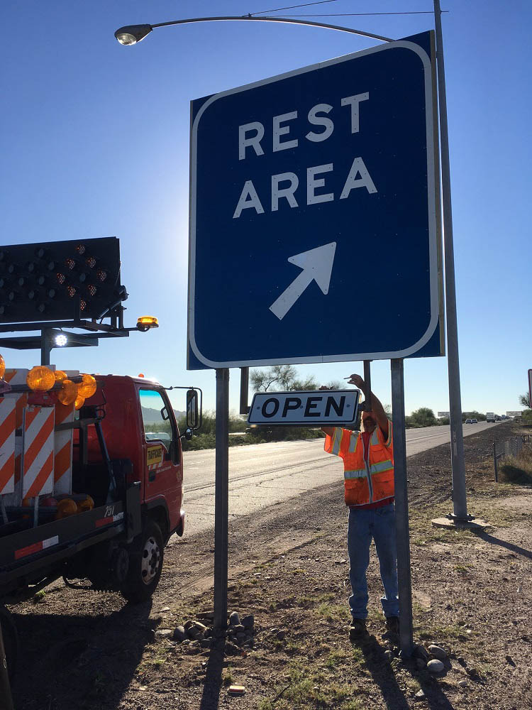 ADOT worker changes closed rest area sign to open.