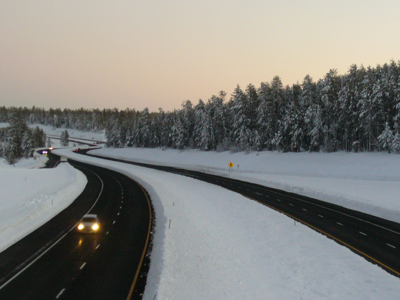 Highway winds through snowy landscape at sunset.