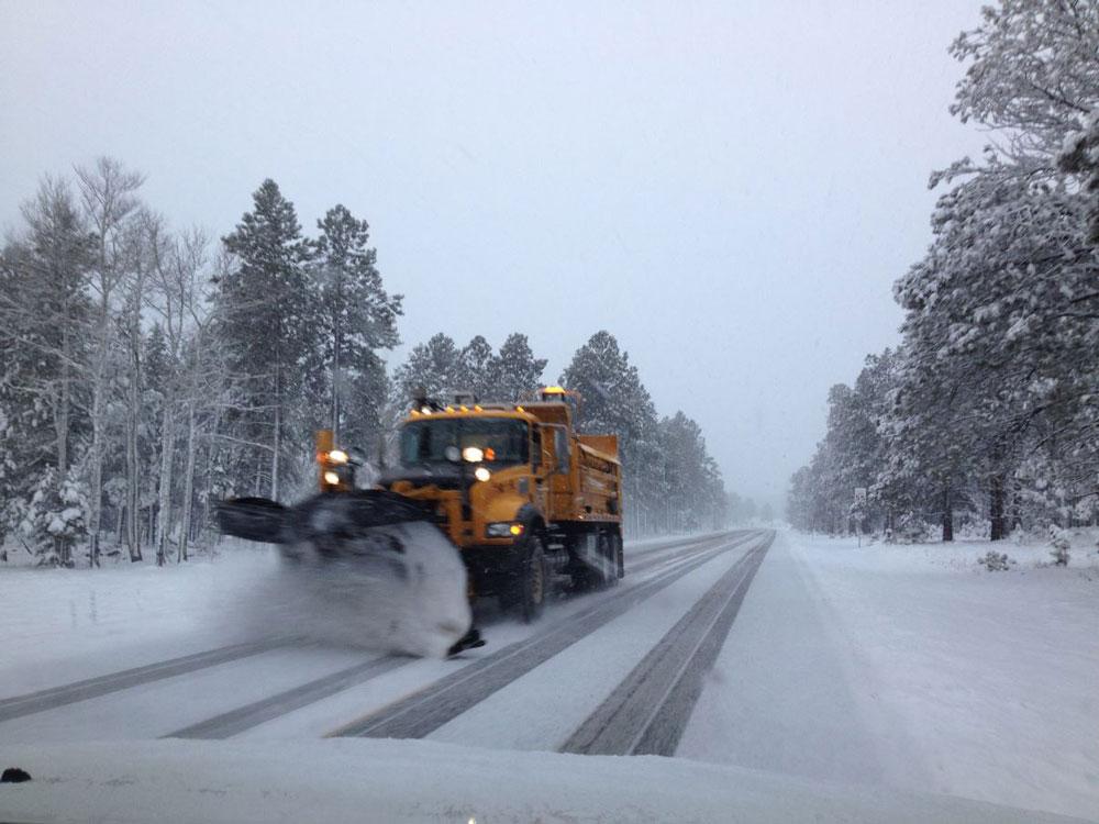 ADOT snowplow clearing roadway.