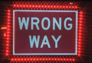 Red Wrong Way sign surrounded by red lights.