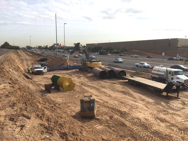 Utility work for South Mountain Freeway: Trucks and Materials in work area along I-10