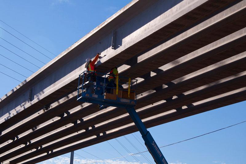 Worker on crane installing girders for Bell/Grand Interchange Project