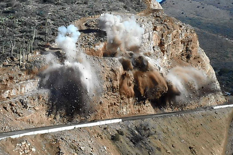 Blasting along State Route 77 to remove overhanging rock