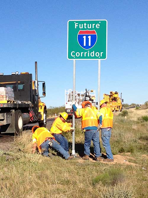 "Workers installing a ""Future I-11 Corridor"" sign by highway"