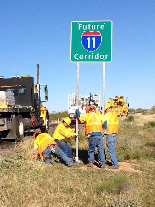Men Installing a Future I-11 Corridor Sign