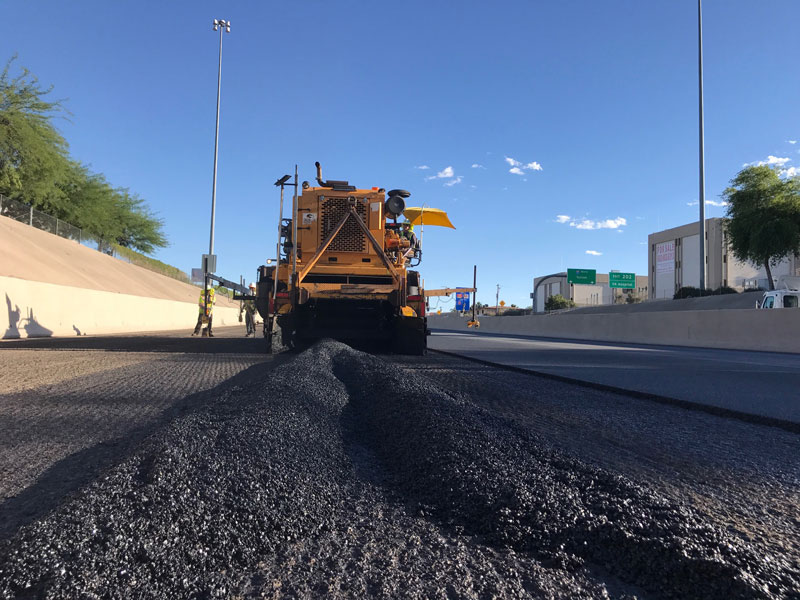 Crews applying rubberized asphalt on freeway